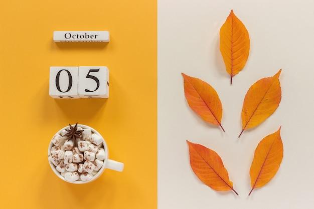 Calendario de otoño 5 de octubre, taza de cacao con malvaviscos y hojas amarillas de otoño