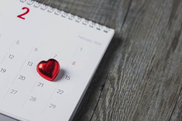 Calendario de papel blanco colocado en un piso de madera gris, vista superior y espacio de copia, tema del día de san valentín