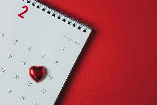 Calendario de papel blanco colocado sobre una mesa roja, vista superior y espacio de copia, tema del día de san valentín