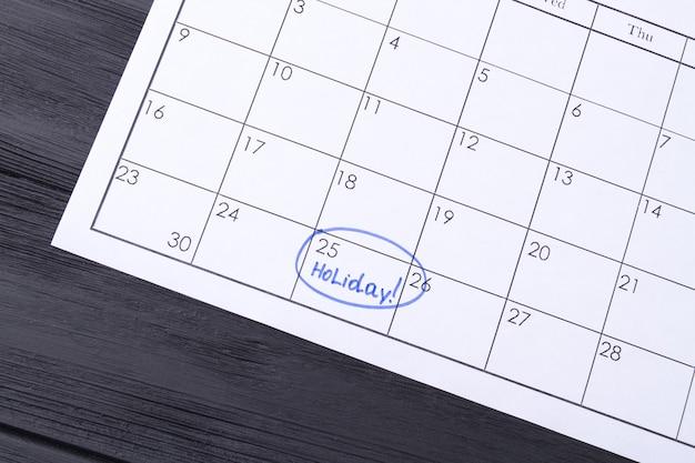 Calendario de papel con un día festivo marcado rodeado por un marcador azul de fondo de madera oscura.
