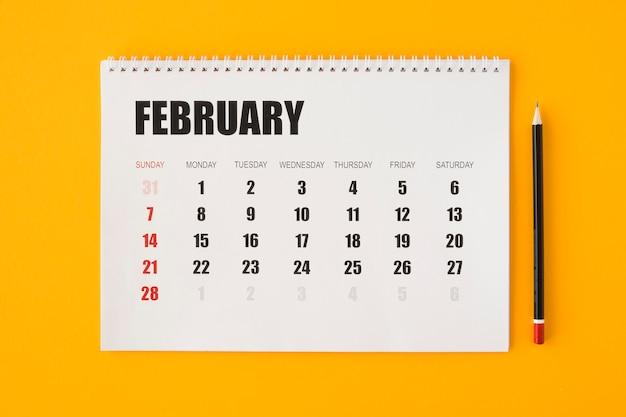 Calendario de papelería de vista superior con lápiz negro