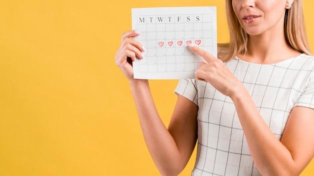 Calendario de períodos con formas de corazón dibujado y hembra