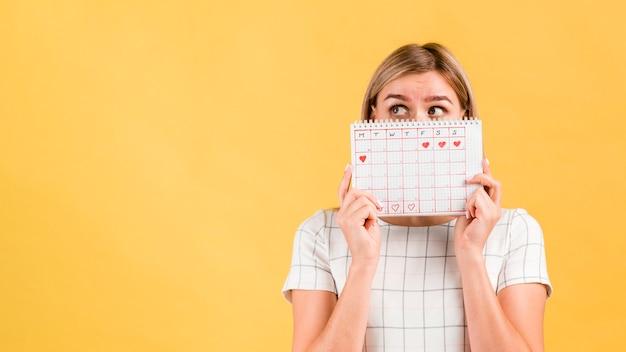 Calendario de períodos con formas de corazón dibujado y mujer cubriéndose la cara
