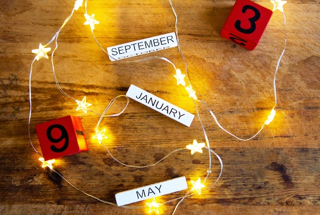 Calendario perpetuo sobre una mesa de madera, diferentes meses y fechas en la pared de guirnaldas en forma de estrella.