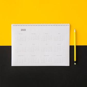Calendario planificador plano laico sobre fondo amarillo y negro