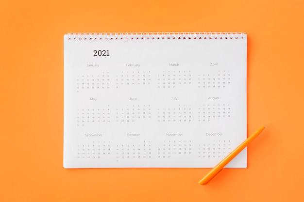 Calendario planificador plano laico sobre fondo naranja