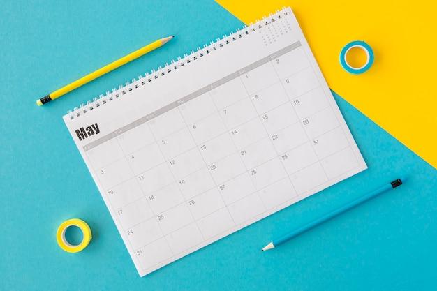 Calendario planificador de vista superior sobre fondo amarillo y azul