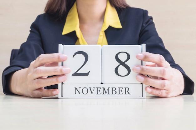 Calendario del primer con la palabra negra del 28 de noviembre en la mano