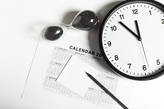 Calendario y reloj sobre fondo blanco.