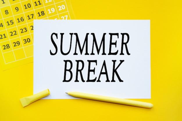 Calendario de resumen, papel, bolígrafo sobre fondo amarillo con texto vacaciones de verano.