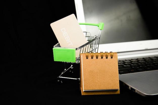 Calendario y tarjeta de crédito o cajero automático en el carrito de la compra plateado en la computadora portátil con fondo.