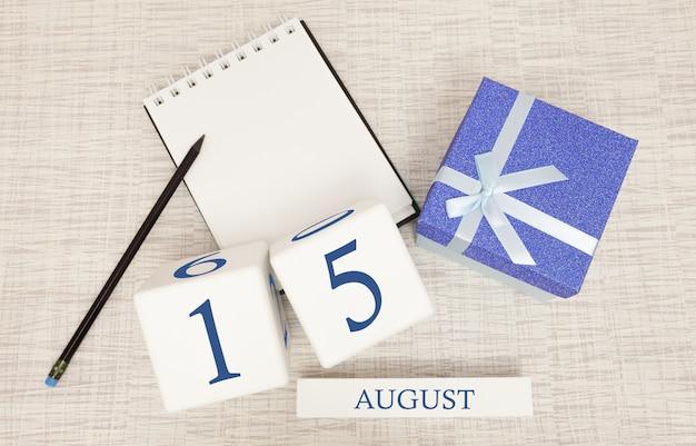 Calendario con texto azul moderno y números para el 15 de agosto y un regalo en una caja.