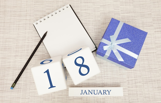 Calendario con texto y números azules de moda para el 18 de enero y un regalo en una caja