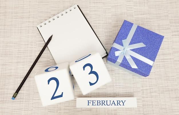 Calendario con texto y números azules de moda para el 23 de febrero y un regalo en una caja.