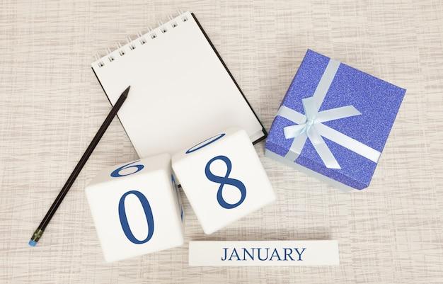 Calendario con texto y números azules de moda para el 8 de enero y un regalo en una caja