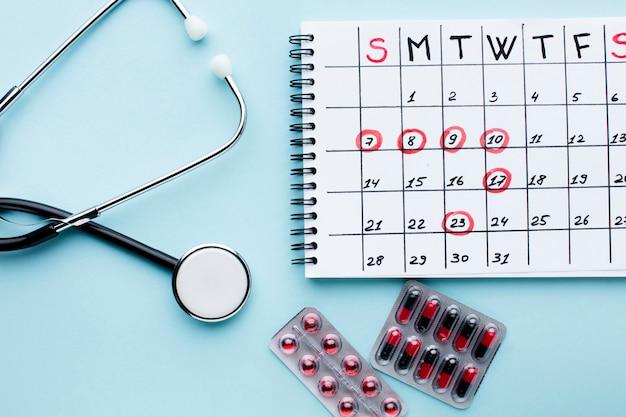Calendario de tratamiento médico con estetoscopio y pastillas.