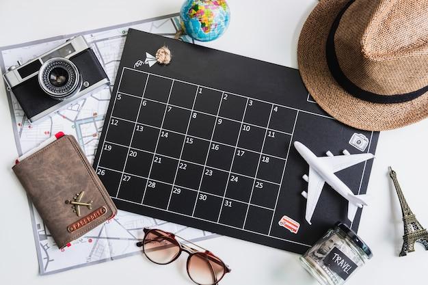 Calendario de vacaciones con cámara y artículos de viaje, vista superior