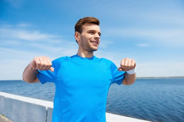 Calentamiento antes de correr. hombre joven guapo haciendo ejercicio mientras está parado al aire libre