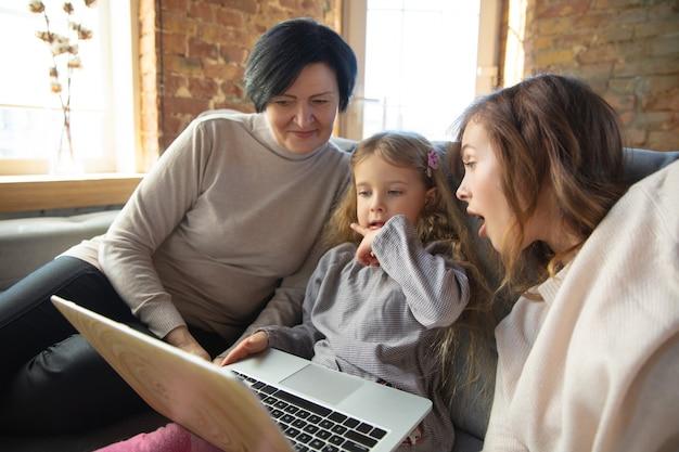 Calentamiento del corazón. familia cariñosa feliz. abuela, madre e hija pasan tiempo juntas. ver cine, usar la computadora portátil, reír. día de la madre, celebración, fin de semana, concepto de infancia de vacaciones.