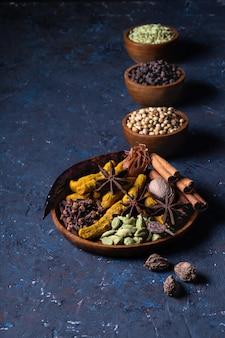 Calentamiento seco de especias indias en placa para otoño invierno comida en hormigón azul oscuro.