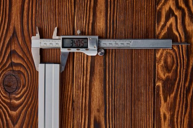 Calibrador a vernier electrónico, mesa de madera, vista superior. instrumento profesional, equipo de carpintero o constructor, herramientas de medición.