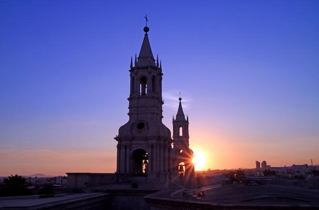 La cálida luz del sol poniente brilla a través del campanario de la basílica catedral de arequipa, perú