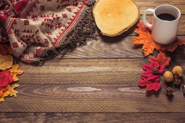 Cálida manta y café cerca de hojas y nueces
