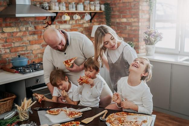 Cálido retrato de una familia joven y feliz que prueban una pizza doméstica. pareja amorosa y sus hijos en la cocina.