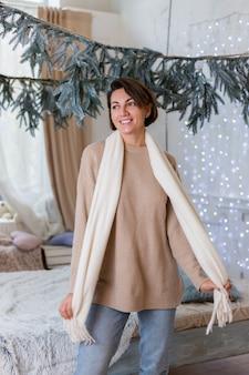 Cálido retrato de mujer feliz en suéter, jeans y bufanda blanca en casa en el dormitorio