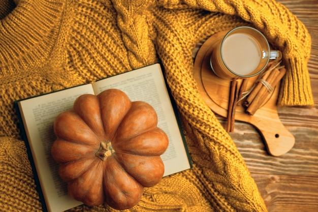 Cálido suéter acogedor, libro abierto y calabaza en madera