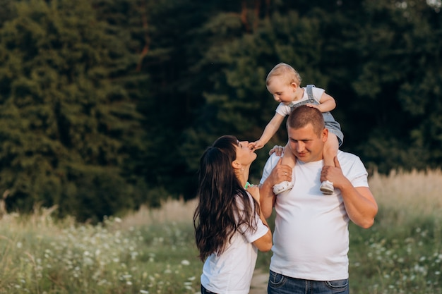 Cálidos abrazos de padres jóvenes y su pequeña hija de pie en el campo de verano
