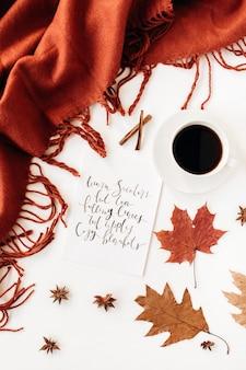 Caligrafía de composición de otoño otoño con taza de café, manta de jengibre, hojas secas, estrella de canela, anís y naranja sobre la mesa blanca