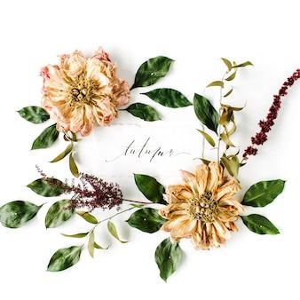 Caligrafía palabra otoño y patrón de corona de marco redondo, flores de peonías secas beige, ramas y hojas aisladas en blanco
