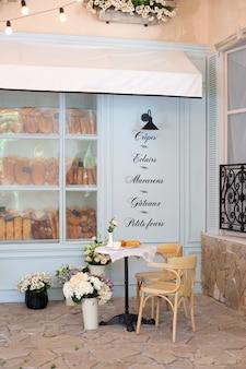 Calle acogedora con mesas de café de estilo francés. por la mañana, desayuno croissant y café en la mesa en la cafetería. fachada de la panadería. restaurante terraza. café de la calle en europa. frente de la cafetería.