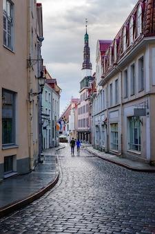 Calle adoquinada medieval con pareja paseando por la calle. tallin, estonia.