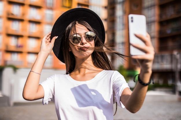 Calle al aire libre de la joven mujer de moda haciendo selfie en la calle, con elegante sombrero de hipster.