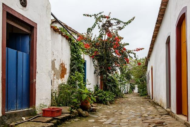 Calle del casco antiguo con flores en las paredes.