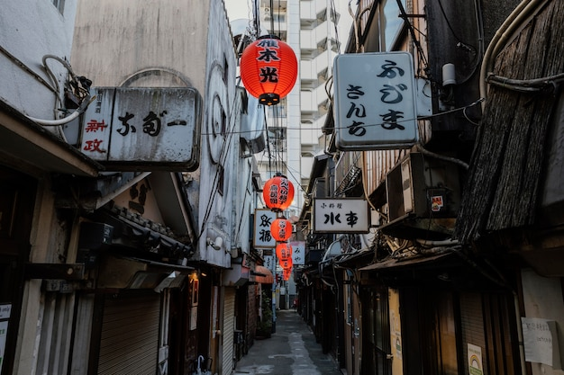 Calle estrecha de japón durante el día con linternas