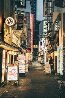 Calle de noche en la ciudad con luces y letreros.