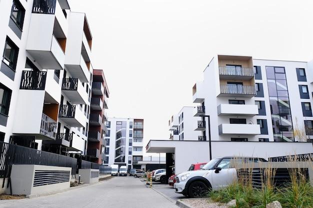 Calle del patio acogedor del distrito de edificios residenciales modernos con coches aparcados.