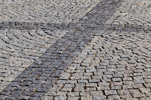Una calle peatonal en la ciudad, hecha de pequeños adoquines de forma cuadrada. en la superficie hay algunas figuras geométricas. primer plano de parte del pavimento