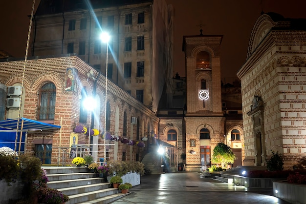 Calle peatonal de noche con iluminación, iglesias, edificios, vegetación y flores en bucarest, rumania
