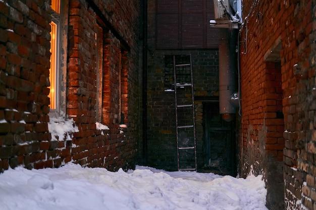 Callejón sin salida cubierto de nieve en el antiguo patio entre las paredes de ladrillo