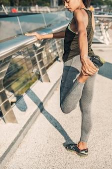 Calma deportista concentrada en el ejercicio de calentamiento al aire libre tirando de su pie hacia arriba