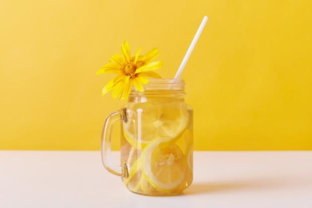 Calma fría de la sed del verano con rodajas de limón y paja
