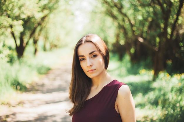 Calma hermosa joven morena con un vestido elegante está caminando y posando en el jardín de verano