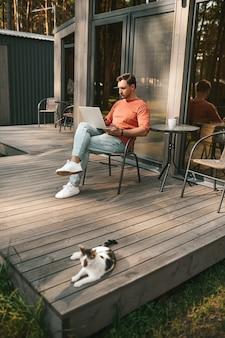 Calma. hombre adulto joven confiado mirando portátil sentado al aire libre en el área de recreación y gato acostado junto a un buen día