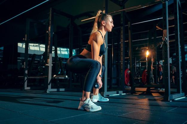 Calma. joven mujer caucásica muscular practicando en el gimnasio con las pesas. modelo de mujer atlética haciendo ejercicios de fuerza, entrenando la parte superior e inferior del cuerpo. bienestar, estilo de vida saludable, culturismo.