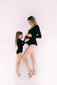 Calma madre embarazada descalza de pie con su hija en monos negros de manga larga similares.