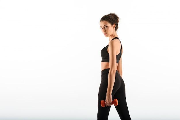 Calma morena rizada fitness mujer sosteniendo pesas